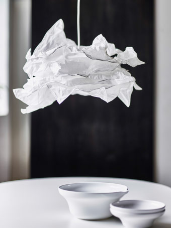 A white lamp shade made of crumbled paper.