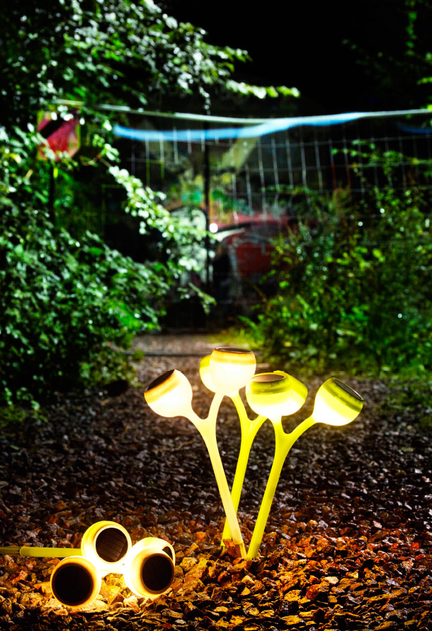 A dark garden with lit LED solar-powered ground sticks that has the shape of a poppy.
