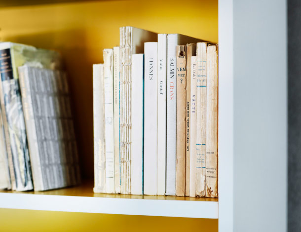 Close-up of a white bookcase with yellow back.