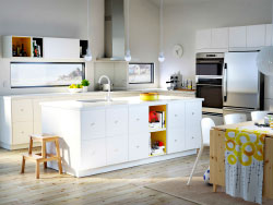 A large sunny kitchen with white drawers, doors, kitchen island and a dining area with dining table in solid pine and white chairs.