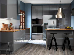 A kitchen with grey high-gloss drawers and doors. Combined with a grey kitchen island and black bar stools.