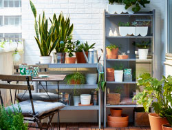 A small balcony with a gray shelving unit and greenhouse, that are filled with green plants and a foldable table with chairs.