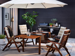 A backyard with brown reclining chairs with beige seat/back cushions and a drop-leaf table