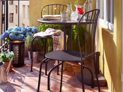 A sunny balcony with gray table and chairs combined with a semi-circular parasol.