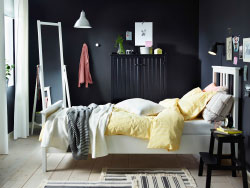 A white bed with bed textiles in white and yellow combined with a step stool and a sideboard both in black.