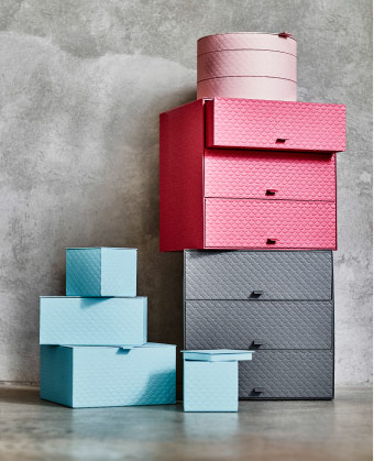 A display of paper board boxes and mini chest of drawers in light blue, dark grey, red and light pink.