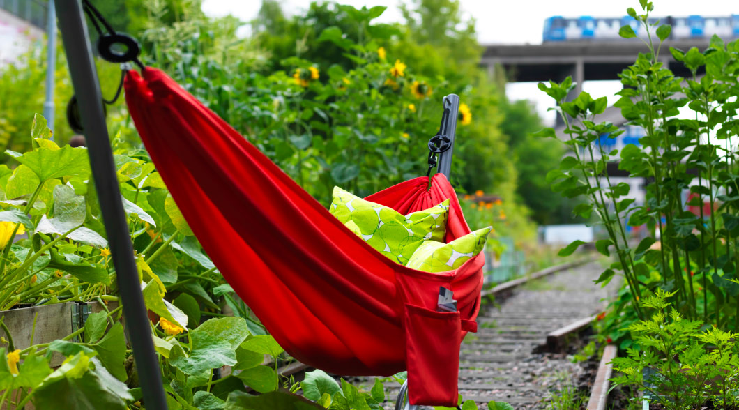 A red hammock with metal stand filled with cushions.