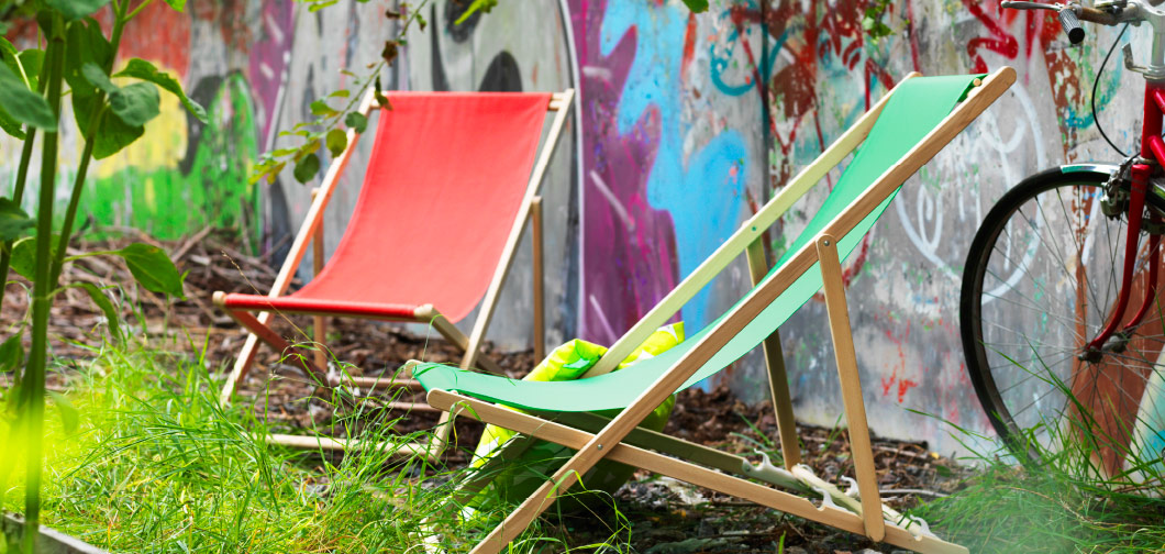 Two wooden beach chairs with red and green fabric.