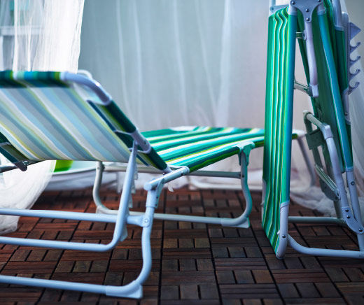 Two sun loungers on a balcony, one is folded.