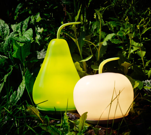 A dark garden with lit LED solar-powered floor lamps that are the shape of apples and pears.
