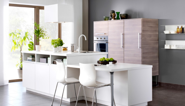 A light kitchen with a white kitchen island and high cabinets in light grey walnut effect.