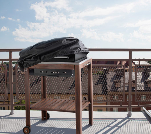 A balcony with a wooden trolley with a charcoal barbecue insert and a black waterproof cover.