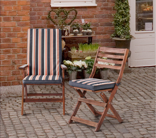 Two striped cushions, one chair cushion and one seat/back cushion, shown together with two brown solid wood chairs.