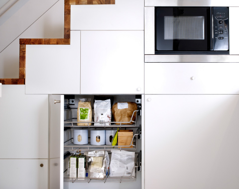 An open kitchen cabinet with wire baskets filled with baking supplies.
