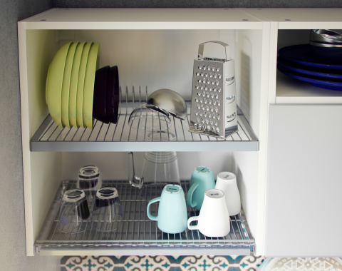 A steel dish drainer with a tray inside a wall cabinet.