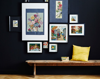 Alt text: View of gallery wall of frames in mix of sizes with wooden bench and yellow cushion.