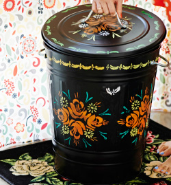 View of customised black KNODD bin on AKERKULLA rug with pattern wallpaper in background.