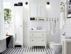 A white bathroom with tiles, sink and high cabinet with mirror door. Combined with a white wash-basin and a wall cabinet with mirror doors.