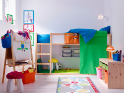 A colourful children's room with a loft bed in solid pine with space underneath for drawing and reading. Combined with low storage in solid pine with plastic boxes in pink, green and orange.