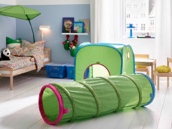 A colourful children's room with a bed in solid beech made with colourful quilt cover and pillowcase and with a green bed canopy that looks like a big leaf. Combined with a green pop-up playing tent and a tunnel.