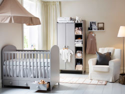A nursery with a light grey cot with drawers and a wardrobe. Combined with a beige bed canopy and a white armchair.