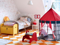 A colourful children's room with a light grey extendable bed, a yellow storage bench that looks like a treasure chest, a red footstool that can be used as a seat and a red playing tent.