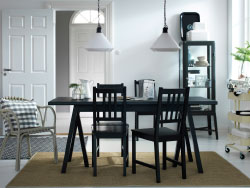 A dining room with a black dining table and chairs. Combined with a beige trolley and a dark grey glass-door cabinet.