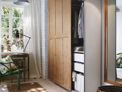 A small hallway with a PAX wardrobe with HURDAL sliding doors in solid pine, and a green ARKELSTORP table.