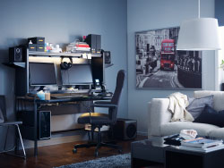 A black workstation with space for two screens, speakers and storage on top, shown inside a living room.
