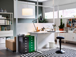 A home office with a white desk that is adjustable in height. Combined with a black standing support stool and drawer units in grey and green.