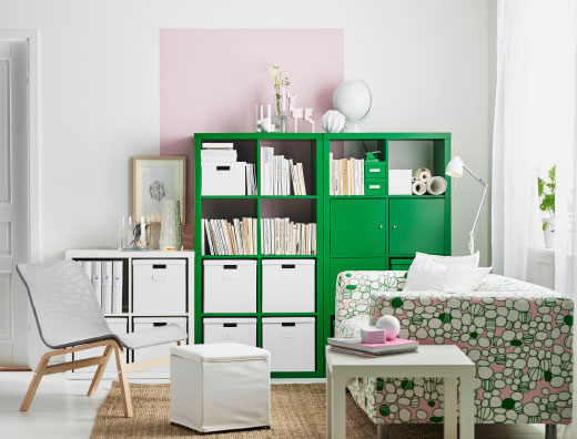 A living room with green and white shelving units filled with boxes and books. Combined with a two-seat sofa in a pink/green cotton cover and a white side table.