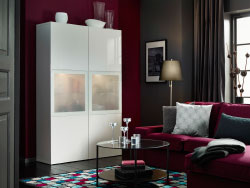 A living room with a white high-gloss storage combination with frosted glass doors and a red-lilac two-seat sofa with chaise longue. Combined with a high pile rug with square pattern in grey, red-lilac, white, turquoise and blue.