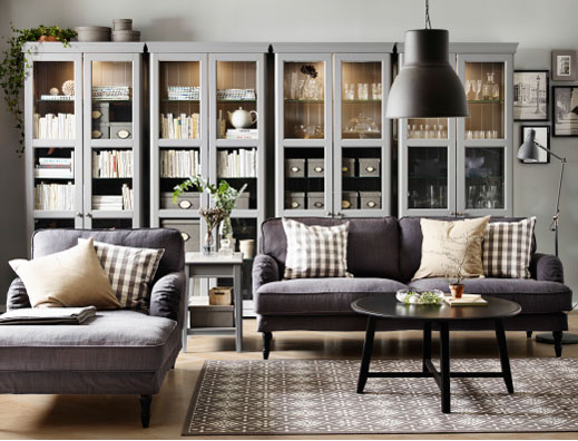 A living room with a grey two-seat sofa, chaise longue and a black round coffee table. Combined with four grey glass-door cabinets.