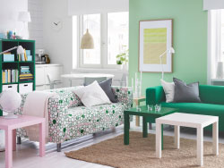 A bright living room with two two-seat sofas, one with a green cover and one with a fun pattern in green, pink and white. Combined with small side tables in green, white and pink.