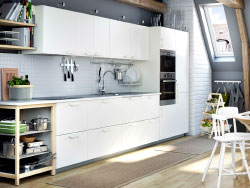 A white kitchen with light grey worktops. Combined with stainless steel extractor hood, microwave oven and oven.