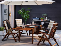 A backyard with brown reclining chairs with beige seat/back cushions and a drop-leaf table.