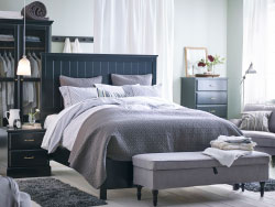A large bedroom with a big black bed standing in the middle of the room, with gray bed textiles. Combined with chest of drawers in differend sizes and a wardrobe with tempered glass doors, all in black.