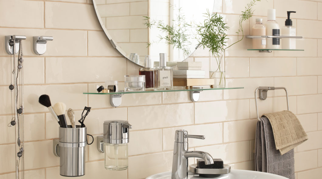 A bathroom with knob hangers, soap dish, towel hanger, toothbrush holder, soap dispenser and shelves in chrome-plated steel and tempered glass.