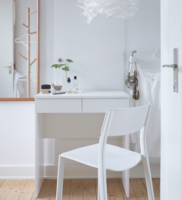 A white dressing table with white chair in front.