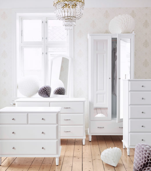 A line-up of white chests of drawers and a wardrobe
