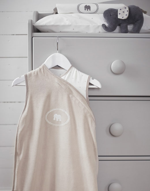 A beige/white sleeping bag for a baby, hanging on a chest of drawers.