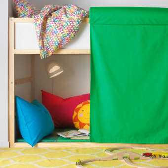 A green curtain with a cushion at the top, hanging on the side of a bunk bed.