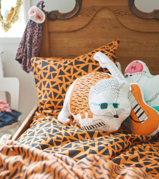 A bed with black/orange quilt cover and cushions shaped as a guitar, hedgehog and a bulldog.
