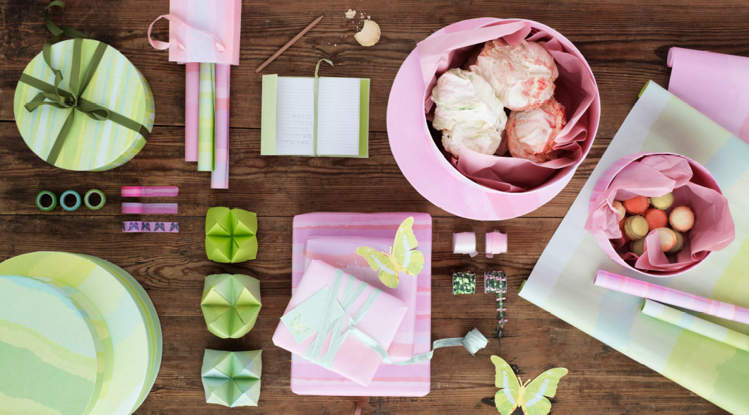 A display of pink and light green gift boxes, gift wrap, notebooks and butterfly decorations.
