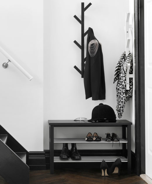 A small hallway with a wall hanger with the shape of a tree and a bench with shoe storage, both in black.