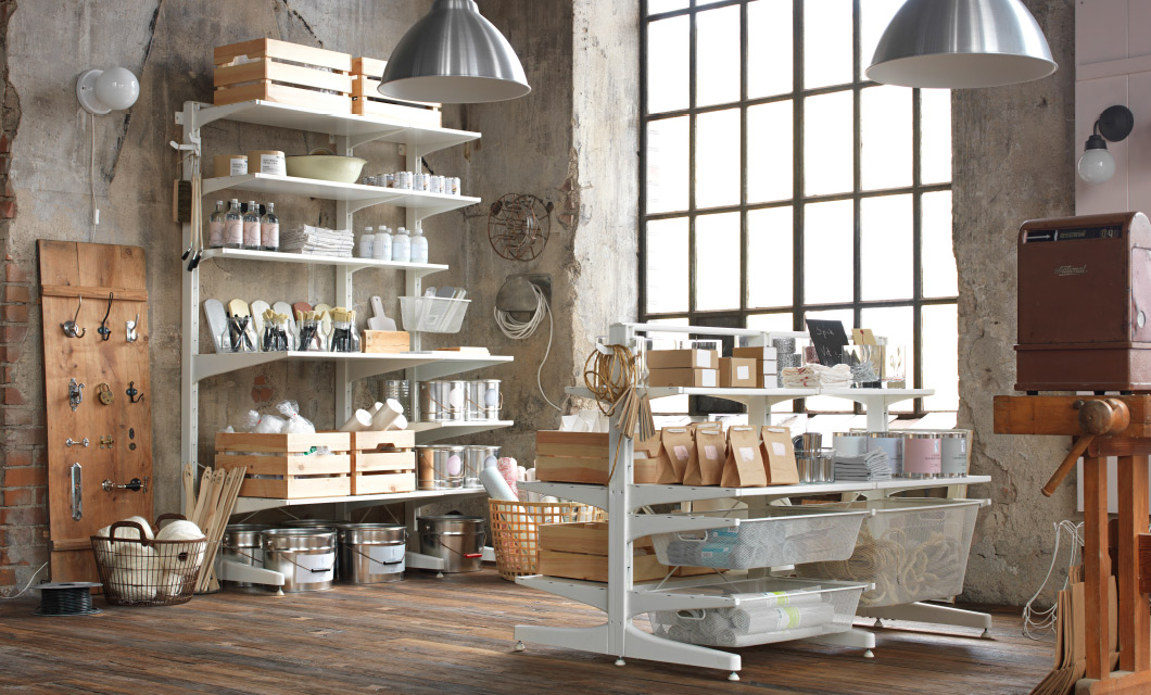A shop with a white wall-mounted shelf solution and a free-standing solution with mesh baskets.