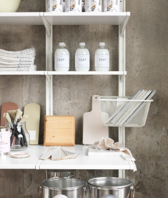 A white wall-mounted shelf solution with mesh baskets.