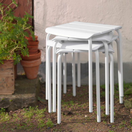 A backyard with a pile of white outdoor stools.