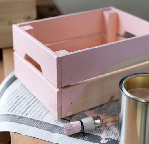 A storage crate in untreated solid pine that has been painted pink.