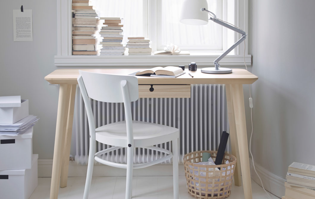 A light room with a desk in ash veneer and a white chair.